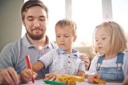 childcare: Young man and little girl looking at cute boy drawing