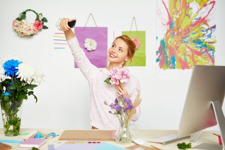 artistic addiction: Young designer with bunch of hydrangea making selfie at workplace