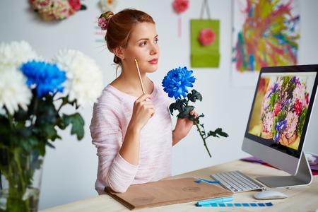monitor de computadora: Diseñador pensativo con el lápiz y el azul del crisantemo de pie delante de monitor de la computadora Foto de archivo