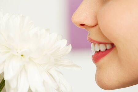 nariz: Mujer joven que goza tierna fragancia de crisantemo blanco Foto de archivo