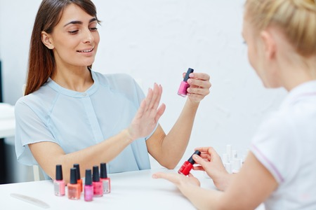 appropriate: Young woman choosing appropriate nail polish Stock Photo
