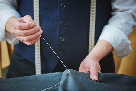 sewing needle: Hands of tailor with thread and needle sewing two parts of clothing