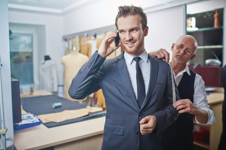 work suit: Young businessman speaking on cellphone while visiting tailor