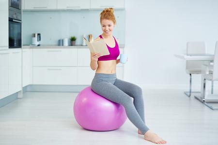 Junge aktive Frau mit einer Tasse Tee und Buch auf Fitness-Ball in der Küche sitzen