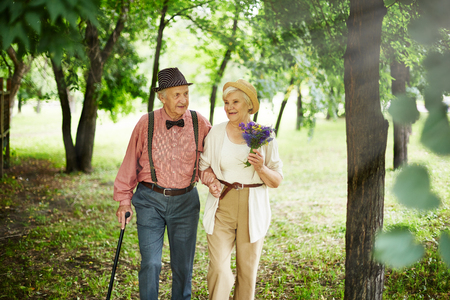 senior men: Affectionate elderly couple taking walk in natural environment