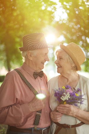 couples outdoors: Amorous seniors looking at one another with smiles in natural environment