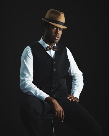 modelos negras: Hombre elegante en sombrero y ropas inteligentes mirando a la cámara