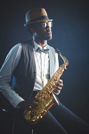 Elegant jazzman in smart clothes and hat holding saxophone