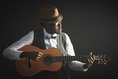 Elegant young man in smart clothes and hat playing guitar