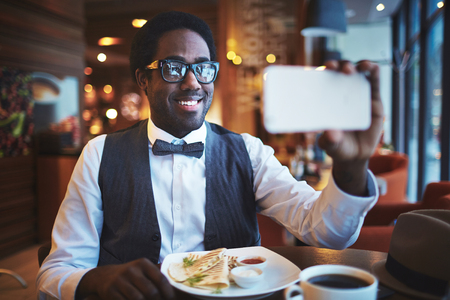 one person only: Elegant young man making selfie while sitting in cafe