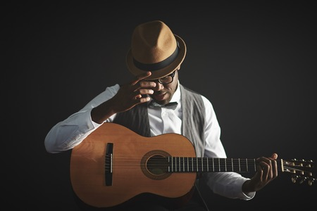 Elegant young man in smart clothes and hat holding guitar Stockfoto