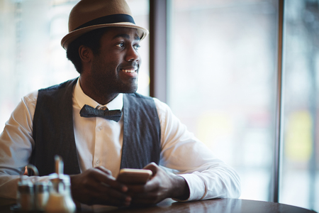 only young men: Elegant young man in hat and smart clothes sitting in cafe Stock Photo
