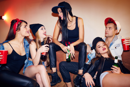 swag: Swag girls with drinks chatting in bar with guy near by Stock Photo