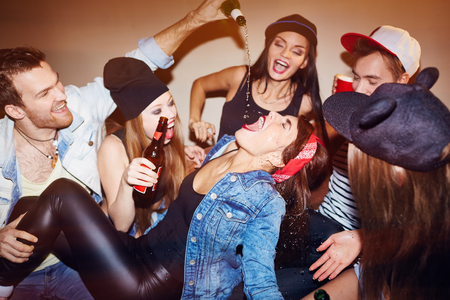 pouring beer: Ecstatic friends pouring beer into girl mouth at swag party