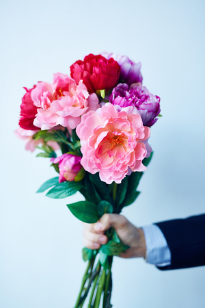 flowers bouquet: Hand of man giving peony bouquet