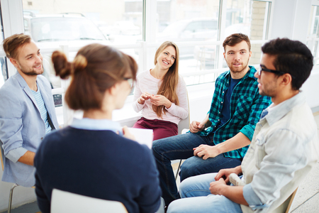 people sitting: Group of young people communicating at psychological course