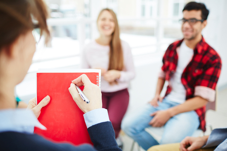 counseling session: Teacher making notes on background of young people at psychological course