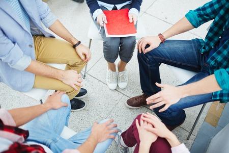 personas sentadas: Grupo de personas que se comunican en el círculo