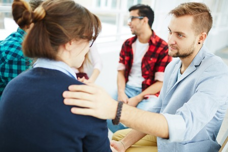 reassuring: Young man reassuring his groupmate at psychological course Stock Photo