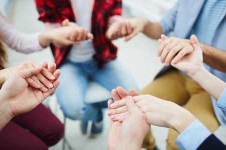 Cirkel van groupmates houden door handen bij psychologische sessie