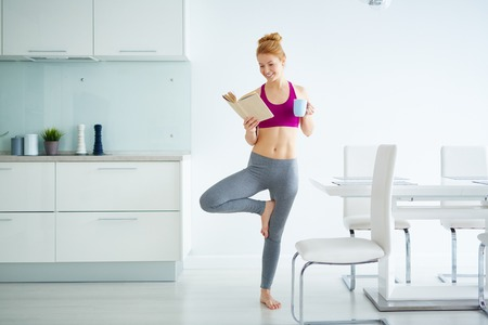 Young active woman with cup of tea and book practicing yoga in the kitchen Standard-Bild