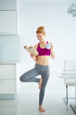 Young active woman with cup of tea reading book and doing yoga exercise in the kitchen Stockfoto