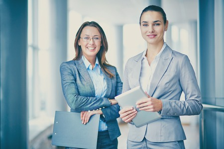 business executive: Two successful businesswomen looking at camera