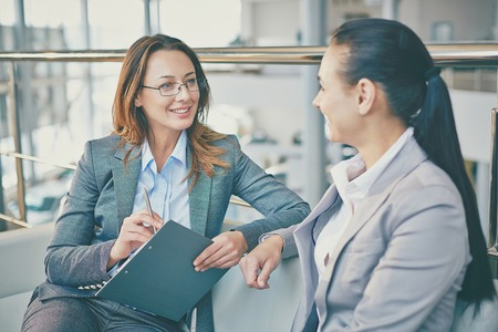 confident woman: Pretty employees discussing information in office