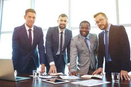 look latino: Happy businessmen in formalwear looking at camera in office