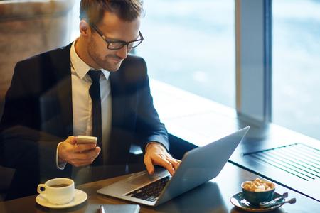hombre de negocios: Joven hombre de negocios moderno con teléfono celular que pulsa en el café