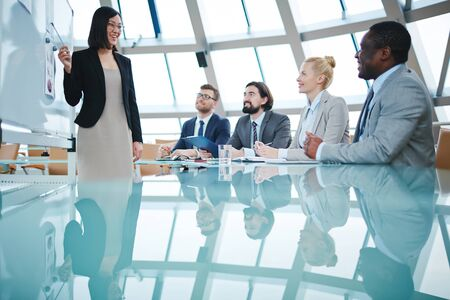 business conference: Young businesswoman pointing at whiteboard and looking at her colleagues at seminar Stock Photo