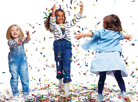 multi ethnic children: Little ecstatic girls playing with confetti Stock Photo