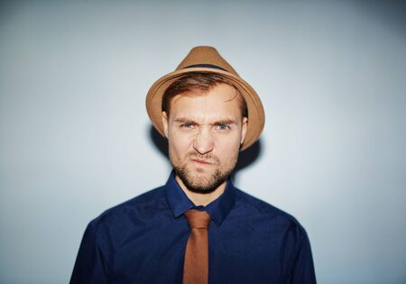 Confused or annoyed guy in hat, tie and shirt looking at camera
