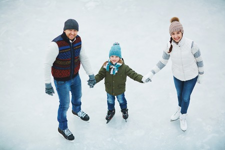 Young couple and their little son skating together