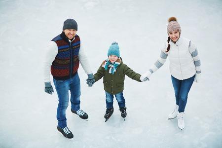 Jeune couple et leur petit garçon à patiner ensemble