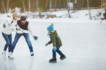 Young parents with stretched arms looking at their son on skating rink