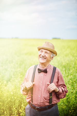 welldressed: Well-dressed senior man standing in meadow Stock Photo