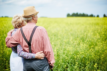 rear view: Rear view of senior couple looking at beautiful blooming meadow in summer Stock Photo