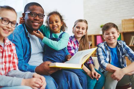 schoolkids: Happy schoolkids and their teacher having reading lesson