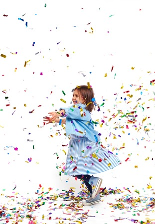 Carefree girl playing with confetti and laughing