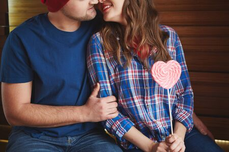 amorous woman: Amorous woman with heartshaped candy flirting with young man Stock Photo