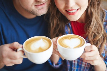 amorous: Amorous dates holding cups with coffee