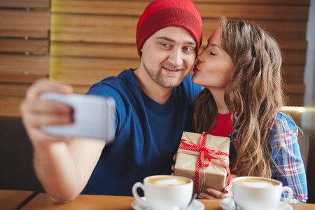 amorous woman: Young man making selfie of his girlfriend and him in cafe Stock Photo