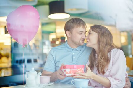 amorous: Amorous man and woman with giftbox celebrating Valentine Day in cafe