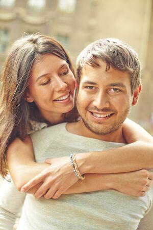 parejas romanticas: Mujer joven amoroso abraza a su novio al aire libre Foto de archivo