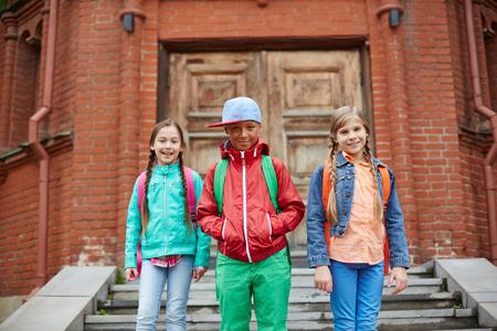 schoolkids: Happy schoolkids with backpacks leaving school