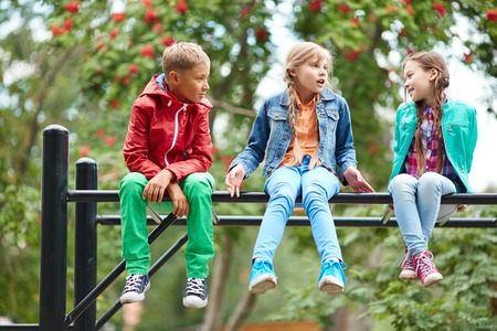 Happy kids talking while sitting on recreational facilities photo