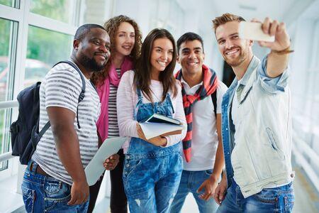 multi ethnic: Friendly students making their selfie in college corridor