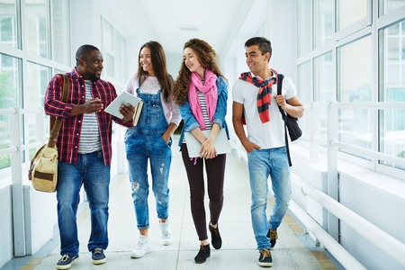group of men: Happy high school learners walking down college corridor and chatting during break
