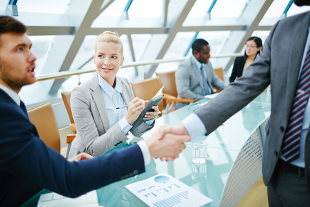 handshaking: Happy businesswoman looking at one of businessman handshaking with partner Stock Photo